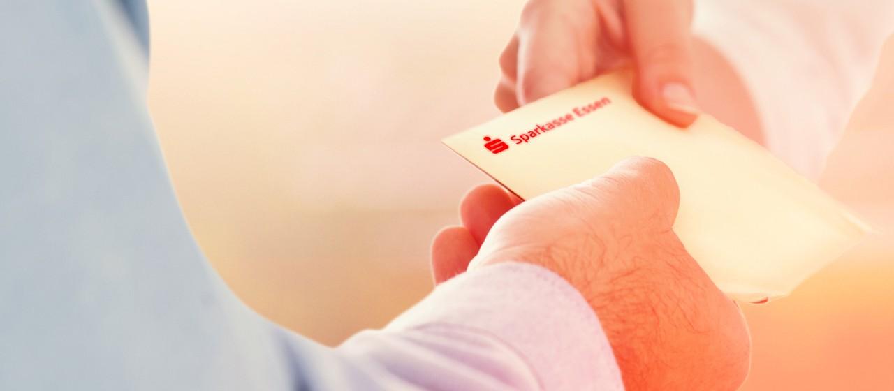 Übergabe eines Umschlages zwischen zwei Menschen.