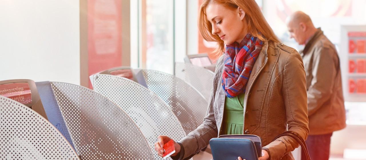 Frau benutzt Ihre SparkassenCard an einem SB-Gerät.